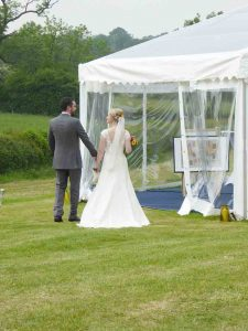 Bride and groom entering wedding marquee midlands